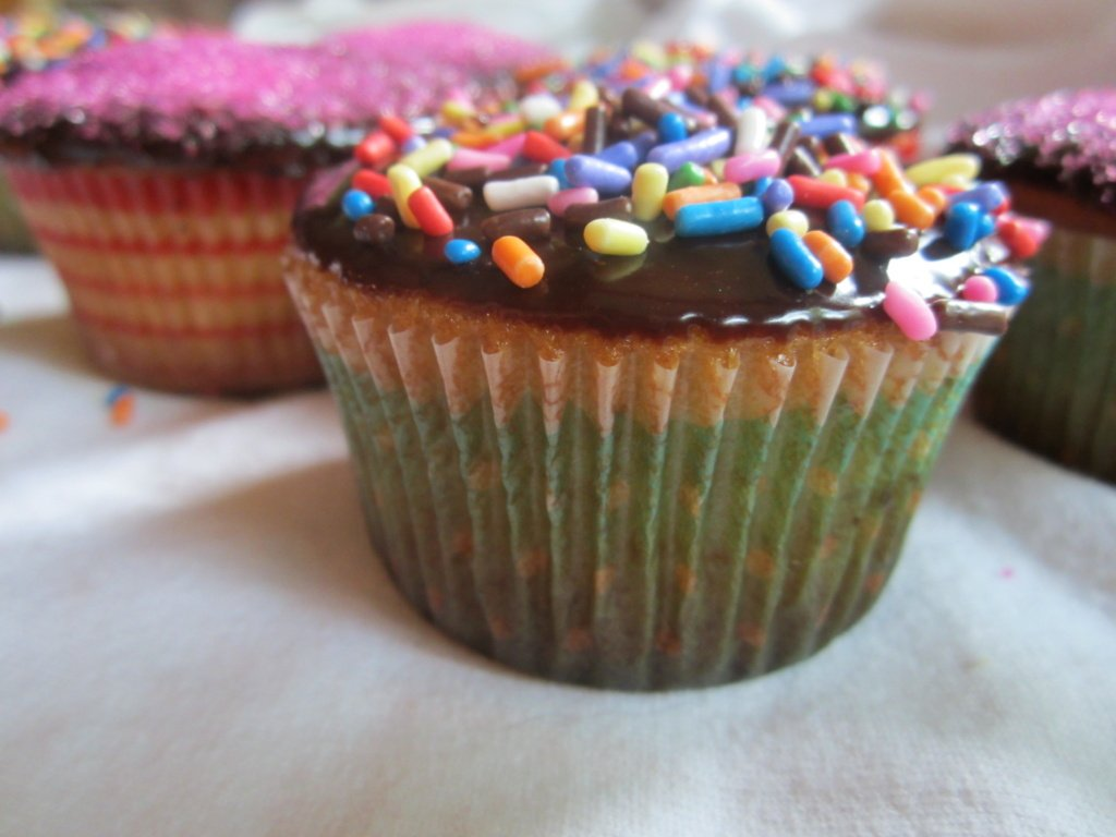 yellow cupcakes with chocolate ganache and sprinkles
