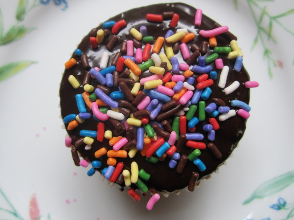 yellow cupcake with chocolate ganache and sprinkles