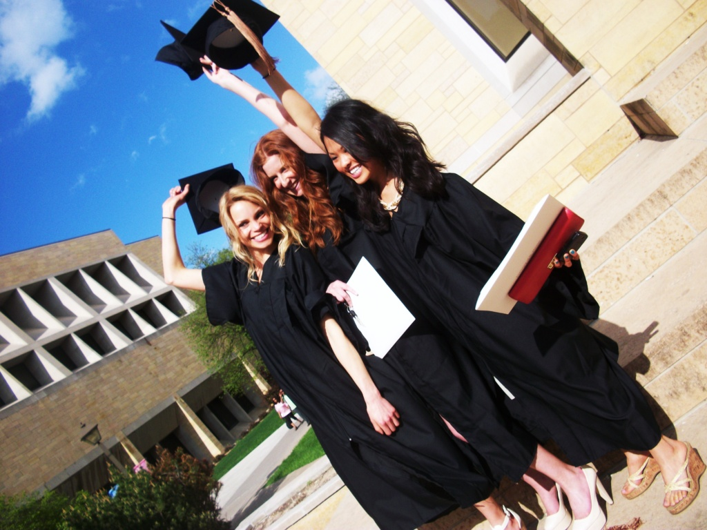 Three girls celebrating in graduation caps and gowns