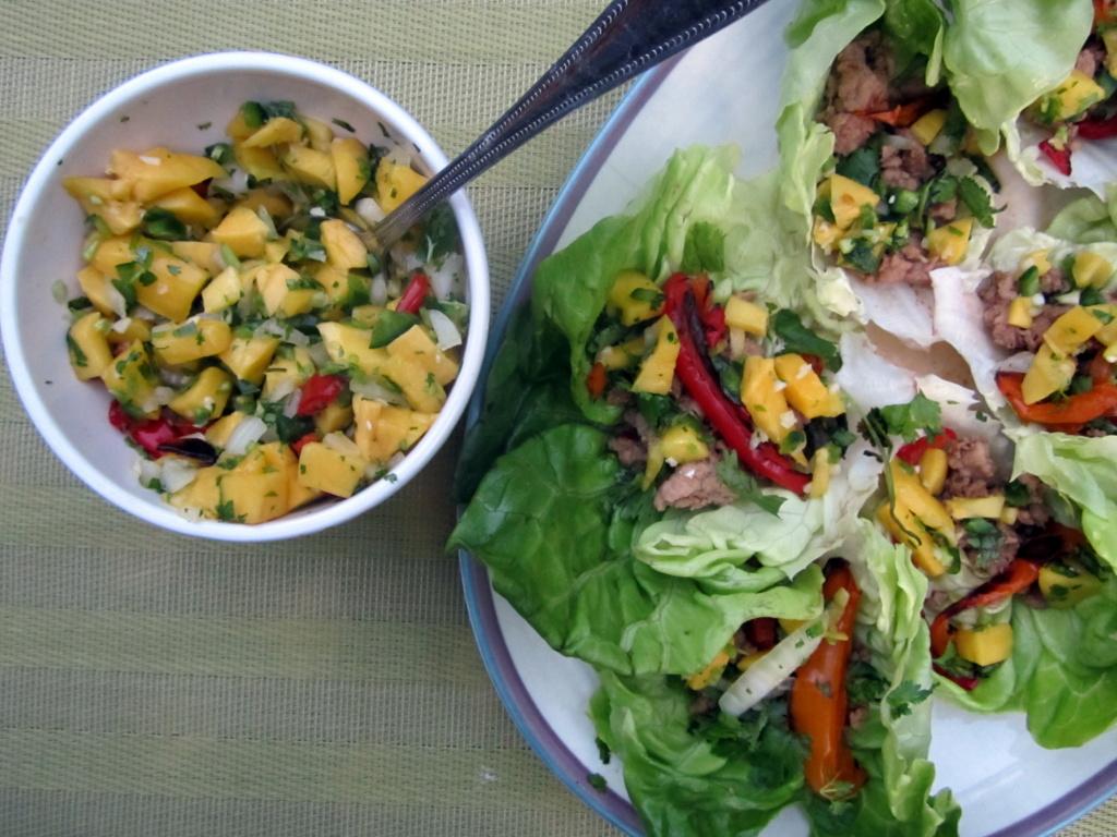 thai chicken lettuce wraps next to a bowl of mango salsa