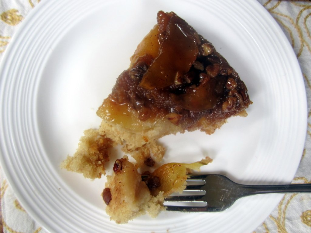 slice of upside-down caramel apple cake on a plate with a fork