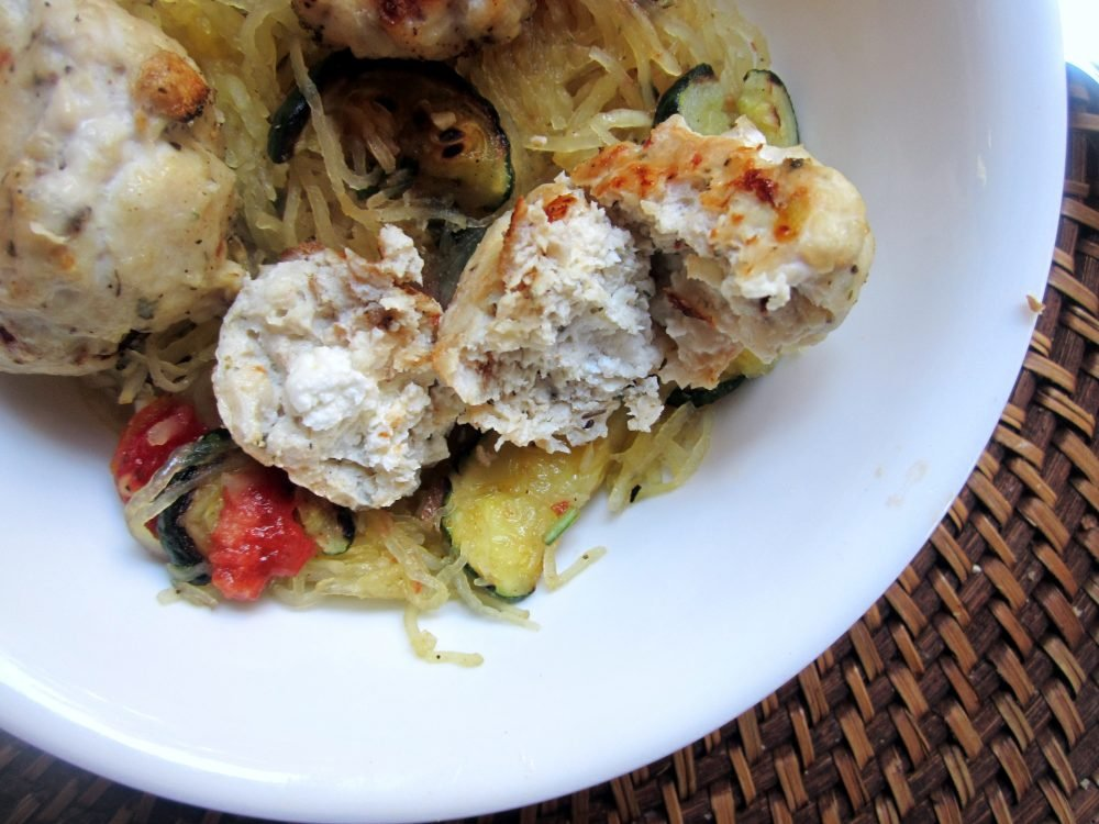 Delicious goat cheese stuffed chicken meatballs served over spaghetti squash with a flavorful basil gremolata salad. This easy dinner is perfect for meal prep and packed with protein.