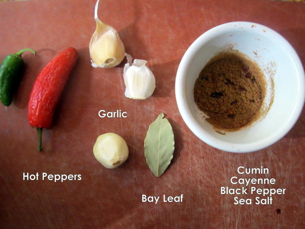 garlic, hot peppers, bay leaf and spices on a table