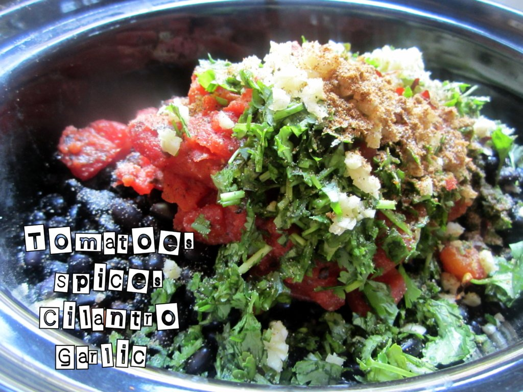 tomatoes, black beans, garlic, cilantro and spices in a bowl