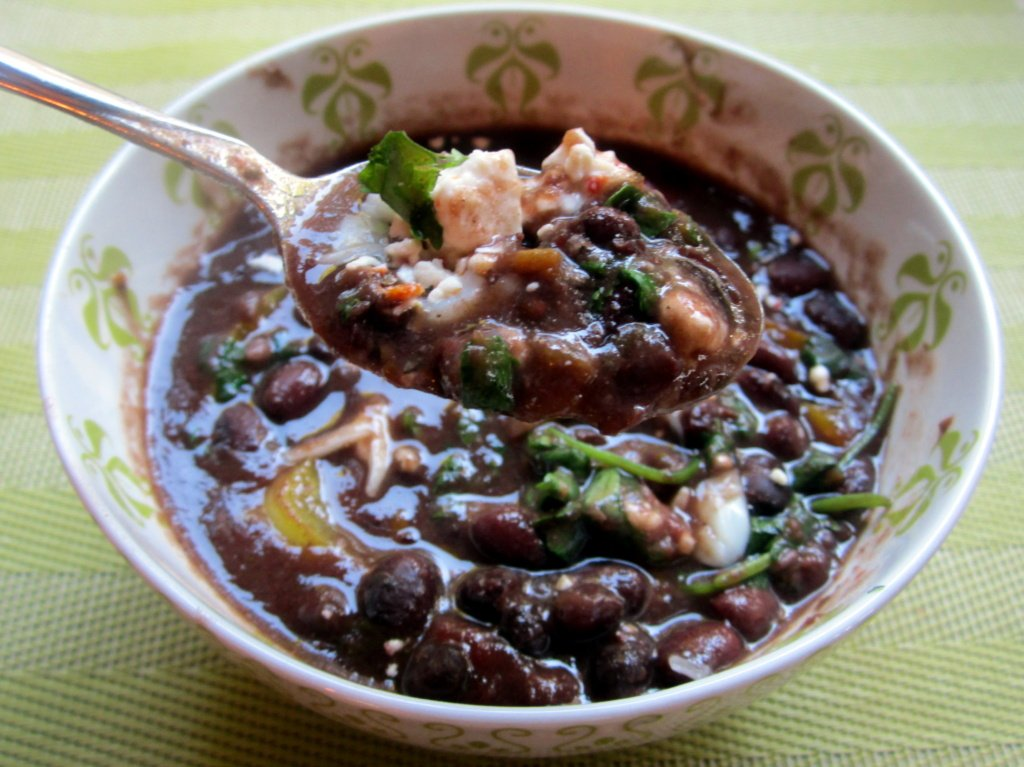 spoonful of caribbean black bean soup coming out of a bowl