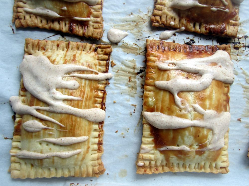 two homemade pumpkin cream cheese pop tarts with frosting