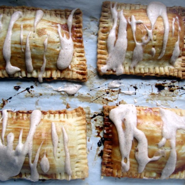 four homemade pumpkin cream cheese pop tarts with frosting