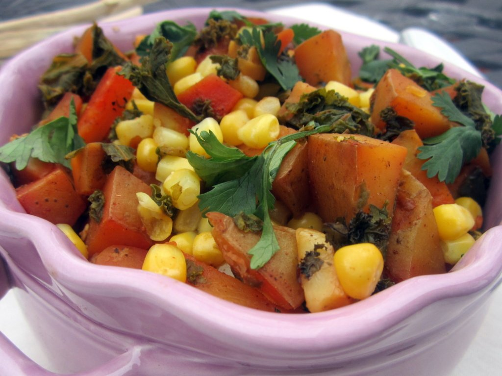 roasted spanish potatoes with corn and kale in a purple dish