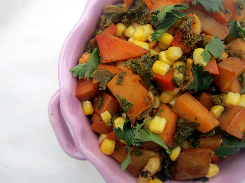 roasted spanish potatoes, corn, kale and red bell pepper in a bowl