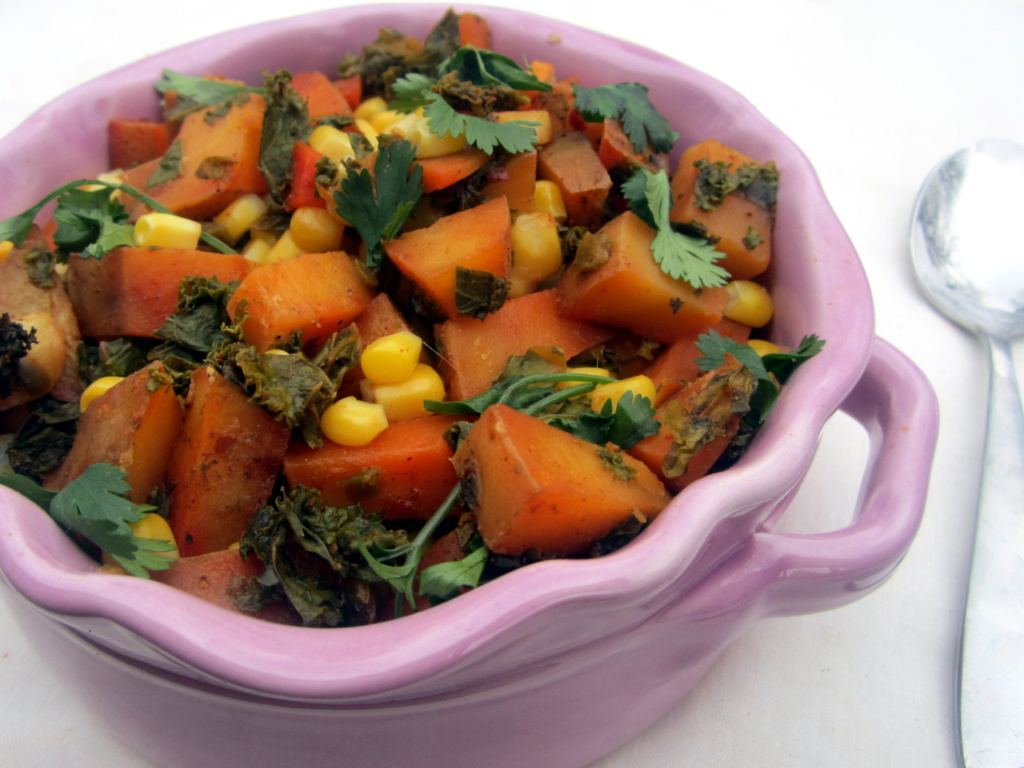 spanish potatoes with kale and corn in a purple bowl