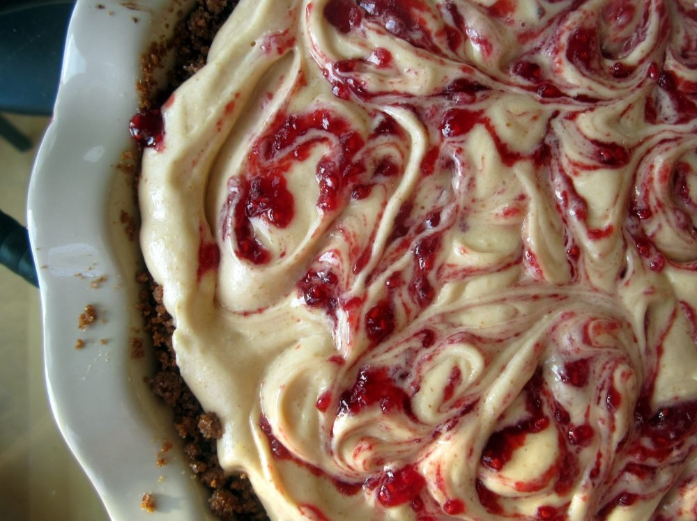Incredible dark chocolate peanut butter pie swirled with sweet raspberry jam all on top of a biscoff cookie crust. This indulgent pie can be eaten straight from the fridge because it's so delicious!