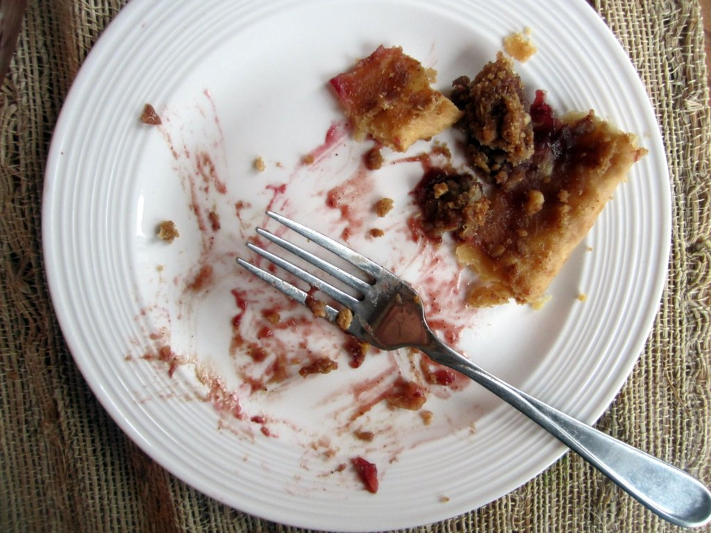 plate with a slice of deep dish bourbon apple cherry pie and a fork
