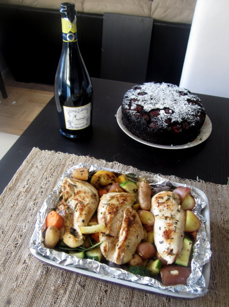chicken and veggies with champagne and cake on a table