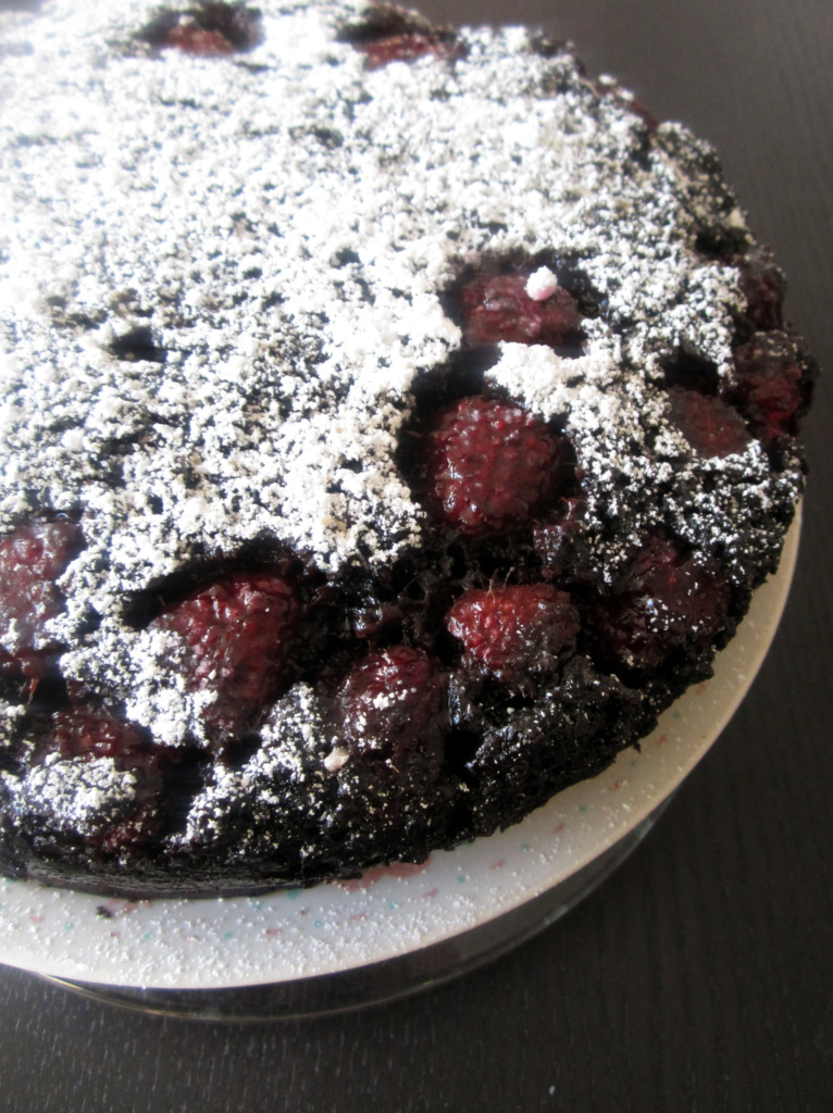 dark chocolate raspberry upside-down cake with powdered sugar on a plate