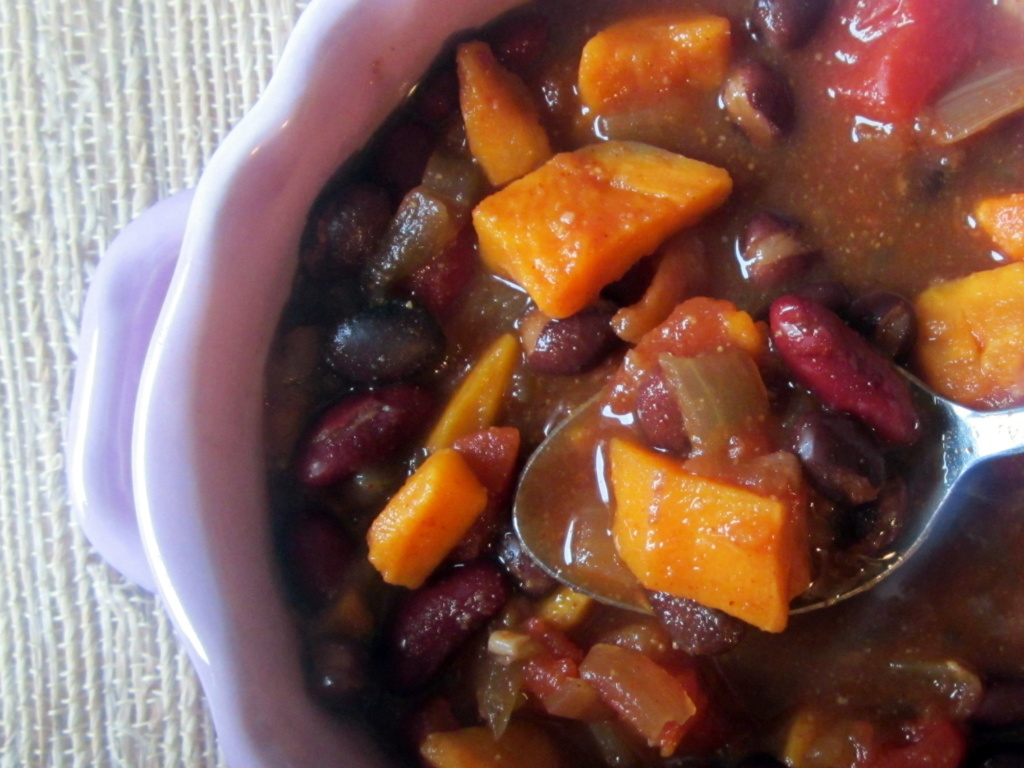 vegetarian sweet potato bean chili in a bowl with a spoon