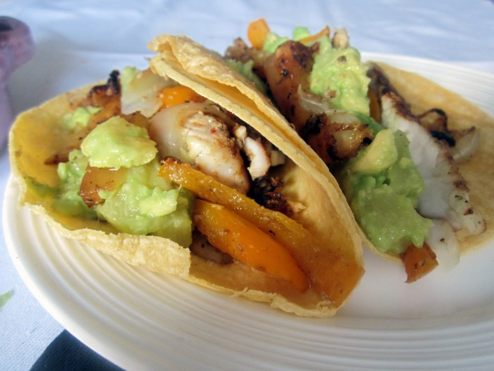 Flavorful spicy fish tacos topped with perfectly sweet mango guacamole. You'll make this fresh and delicious fish taco recipe again and again!
