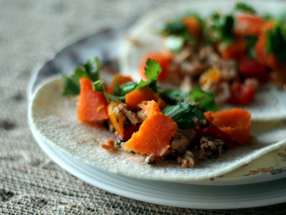Delicious sweet potato & chicken mexican stir-fry made with tons of veggies, delicious spices, and folded into tacos. Skip the takeout and make this easy, healthy recipe for dinner!