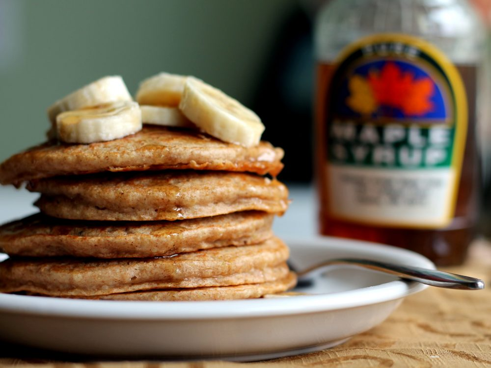 Fluffy whole wheat banana quinoa pancakes in a stack on a plate