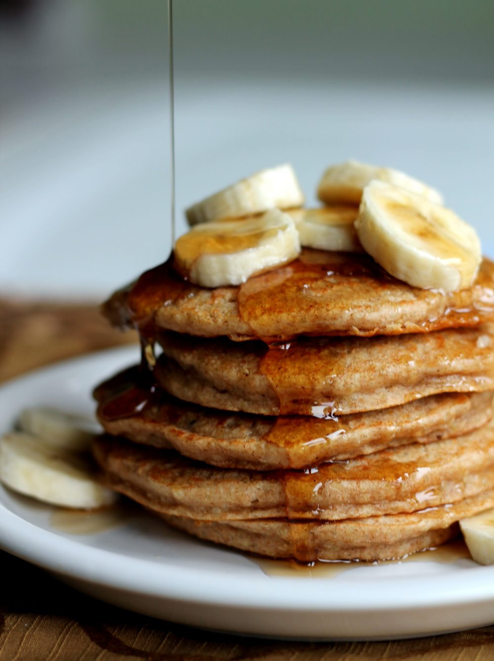 Fluffy whole wheat banana quinoa pancakes being drizzled with syrup on a plate