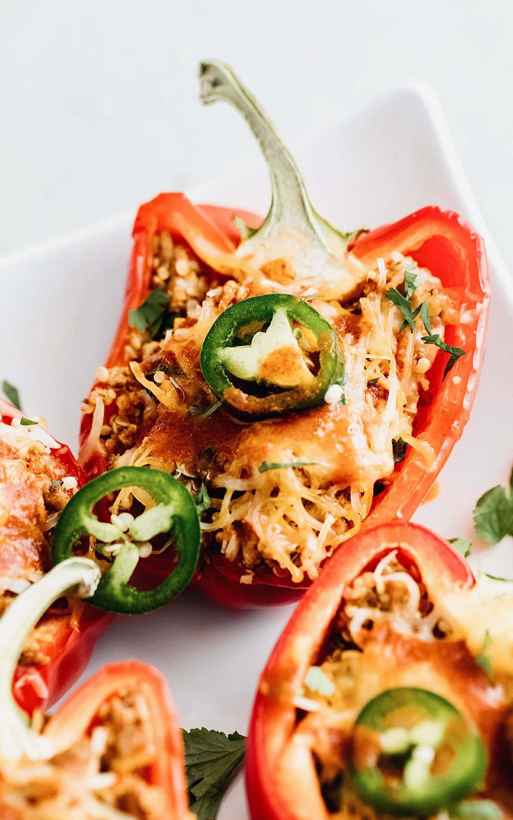 quinoa stuffed bell peppers topped with jalapeño slices