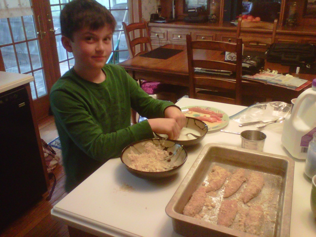 Young boy making chicken fingers