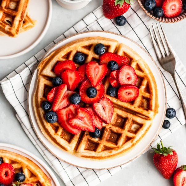 classic buttermilk waffle topped with berries on a plate next to a bowl of berries