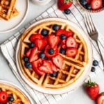 buttermilk waffles on a plate topped with berries