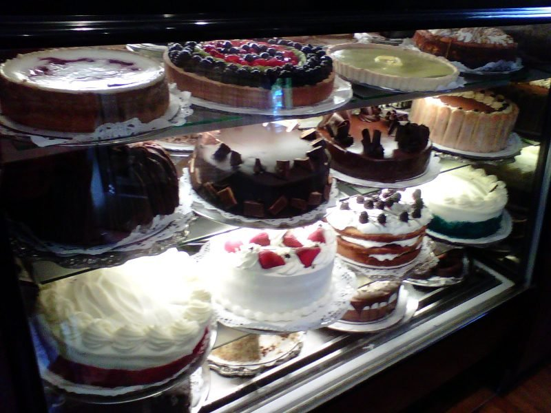 Variety of cakes on display behind glass