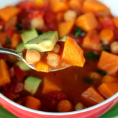 Cozy vegan tomato chickpea soup with hearty sweet potatoes and incredible spices like garlic, cumin, and fresh basil. Top this nourishing soup with avocado for a delicious, filling lunch or dinner.