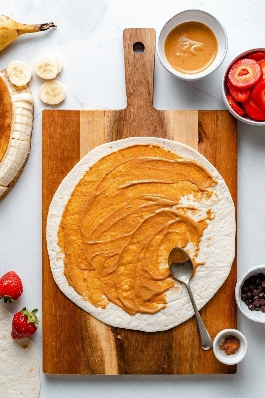 spreading peanut butter on a tortilla to make a strawberry banana quesadilla
