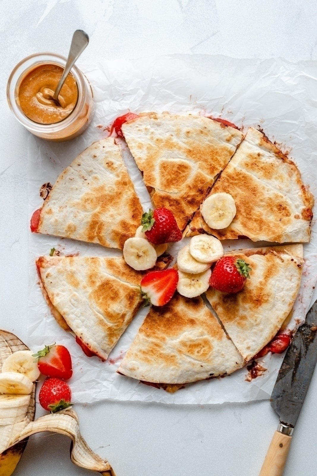 healthy peanut butter strawberry banana quesadilla sliced on parchment paper