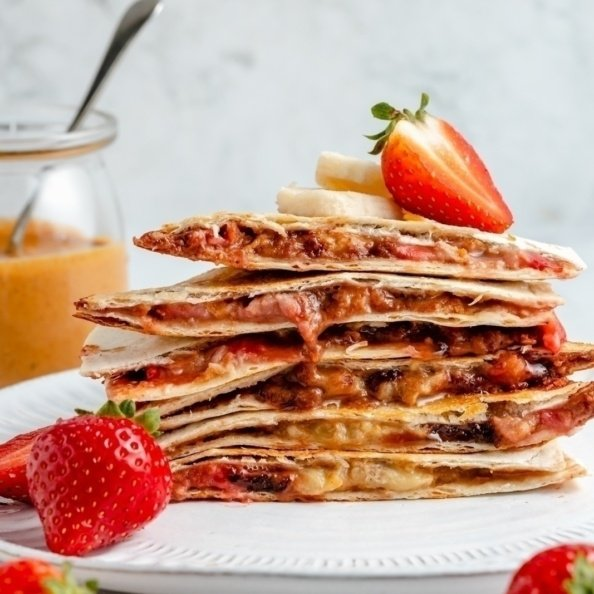 strawberry banana quesadilla sliced and stacked on a plate