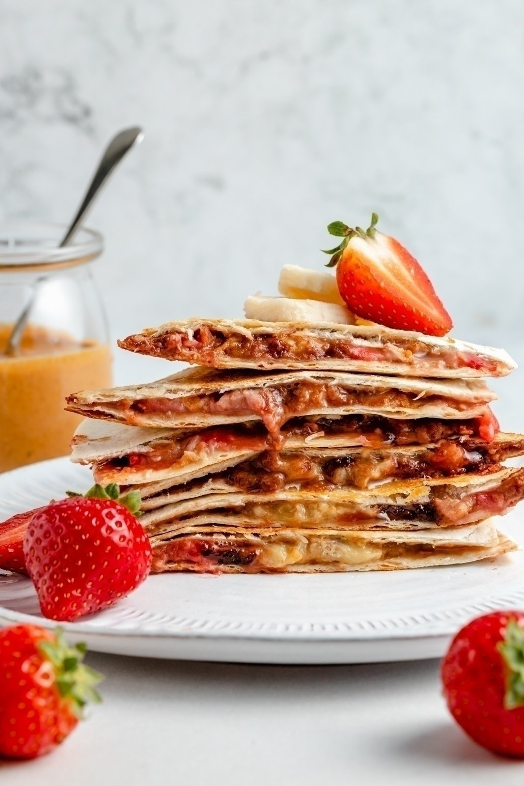 healthy peanut butter banana quesadilla with strawberries on a plate