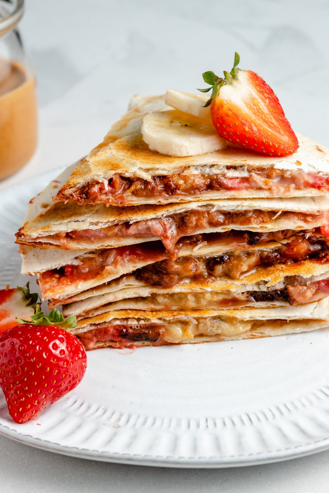 strawberry banana quesadilla stacked on a plate