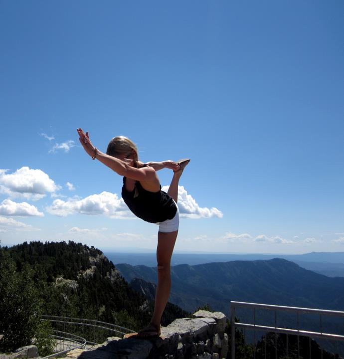 Monique doing a yoga pose on a ledge