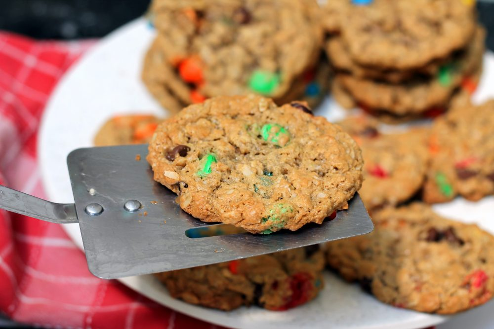 The best monster cookies from the Desserts in Jars Cookbook with oats, delicious peanut butter flavor, and sweet chocolate candies. Add the dry ingredients to a mason jar for a great gift!