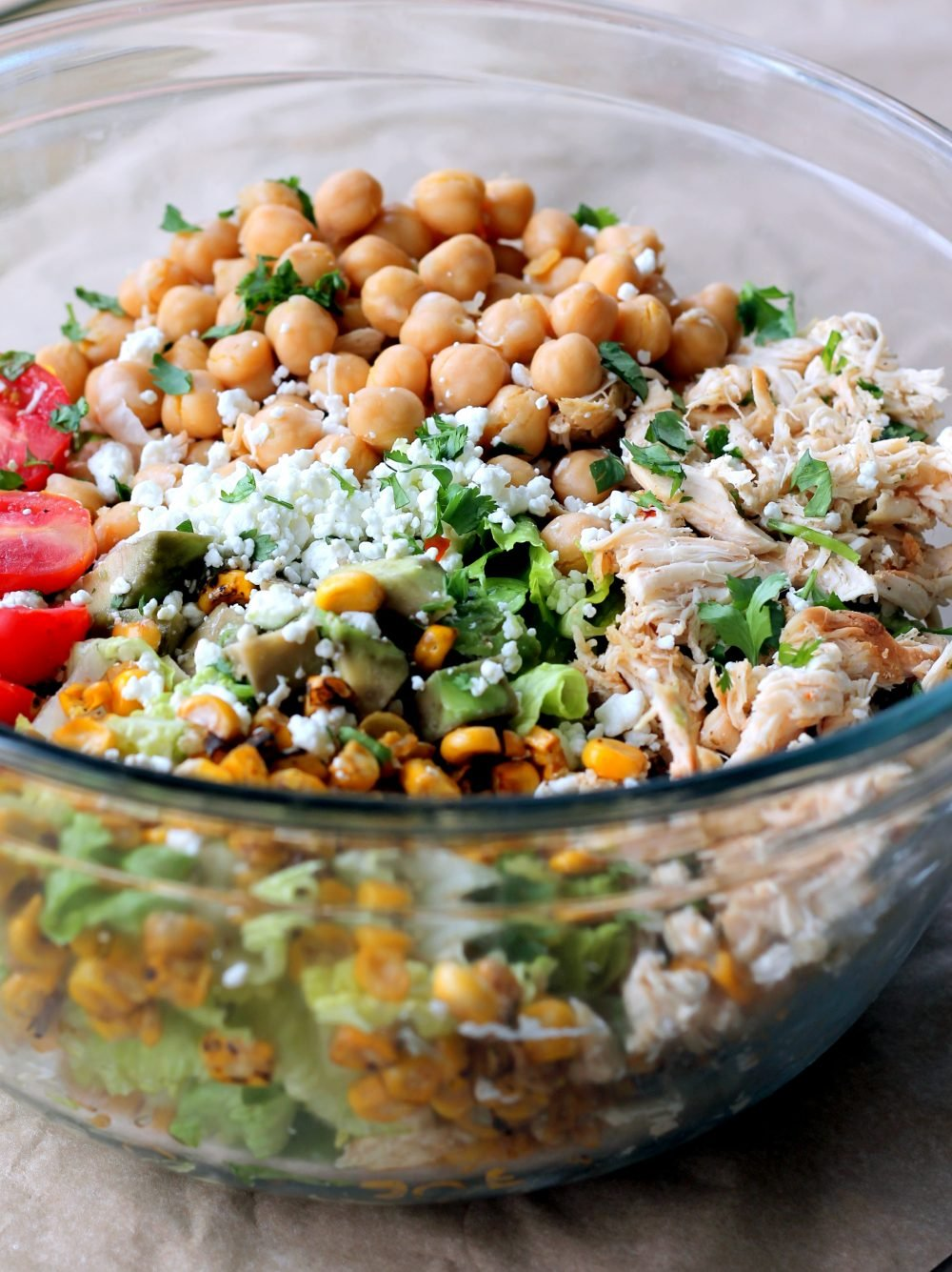 Easy healthy chicken chickpea chopped salad loaded with protein and fresh ingredients like grilled corn, grape tomatoes, crunchy romaine, creamy avocado, and your favorite dressing.