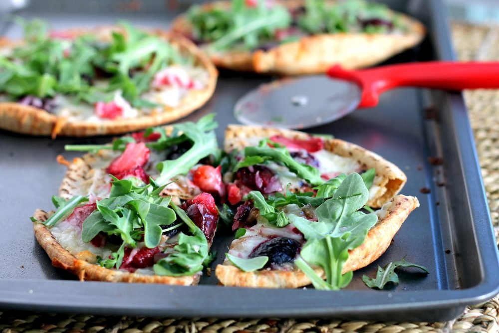 Heavenly roasted balsamic strawberry cherry pita pizzas topped with zippy arugula. The perfect healthy homemade pizzas with incredible flavors!