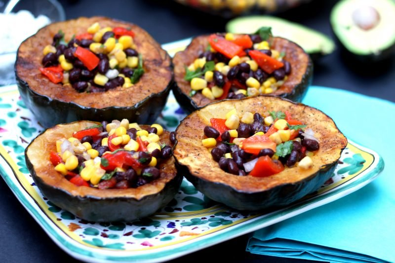 Vegetarian stuffed acorn squash with corn and black beans on a platter