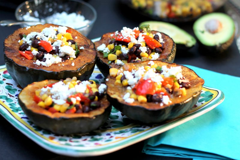 Vegetarian stuffed acorn squash with corn, black beans and goat cheese on a platter