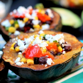 Vegetarian stuffed acorn squash with black beans, corn, red pepper and goat cheese
