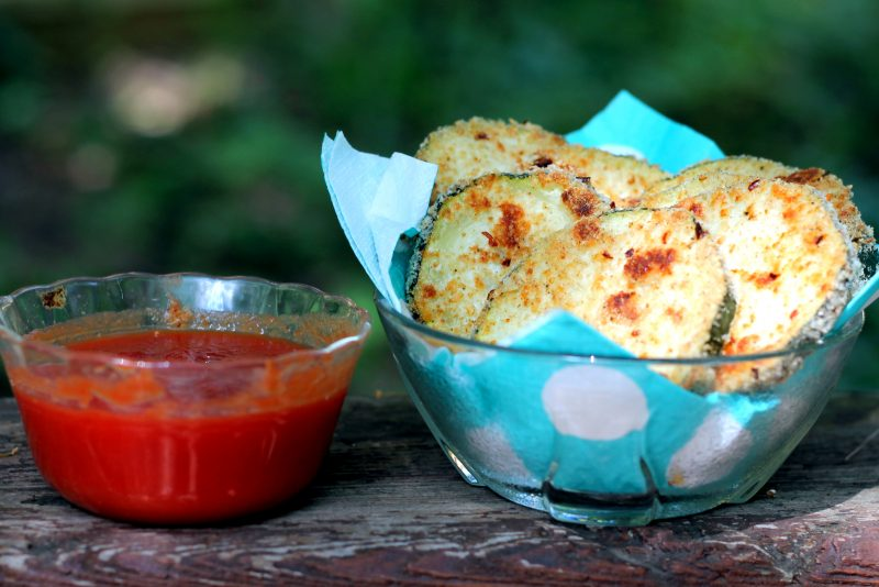 Baked parmesan zucchini chips in a bowl next to marinara sauce