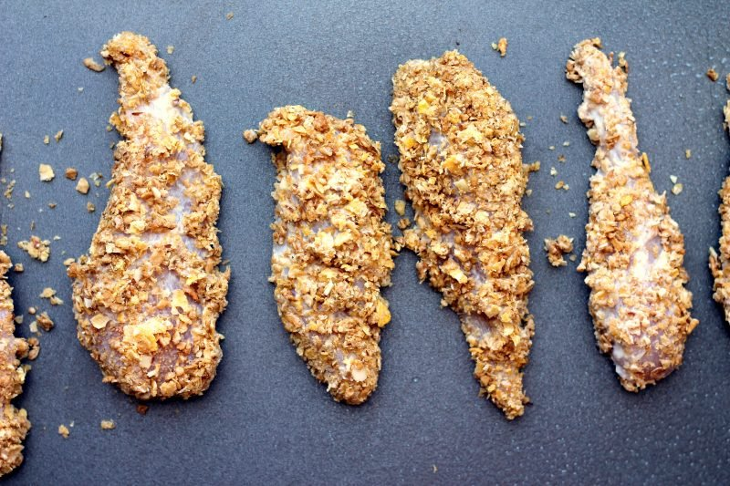Cornflake chicken strips on a sheet pan ready to bake