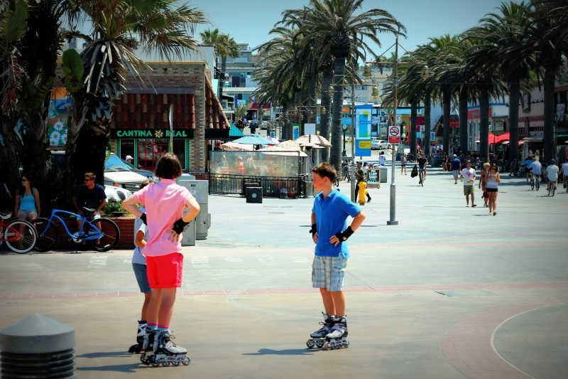 Kids rollerblading on a boardwalk