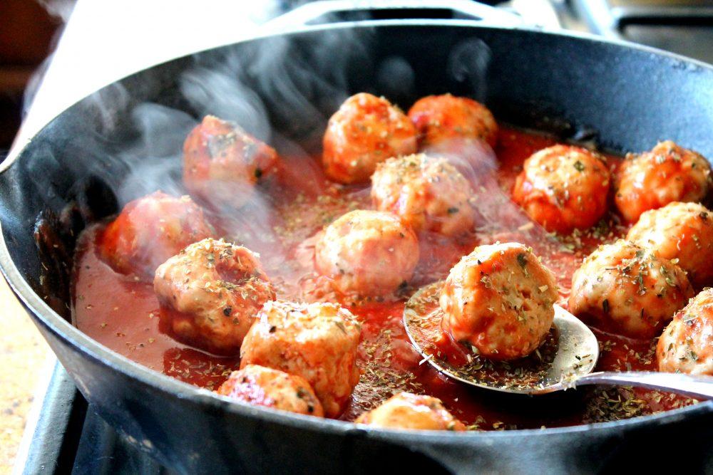 Turkey meatballs in a skillet of tomato basil sauce