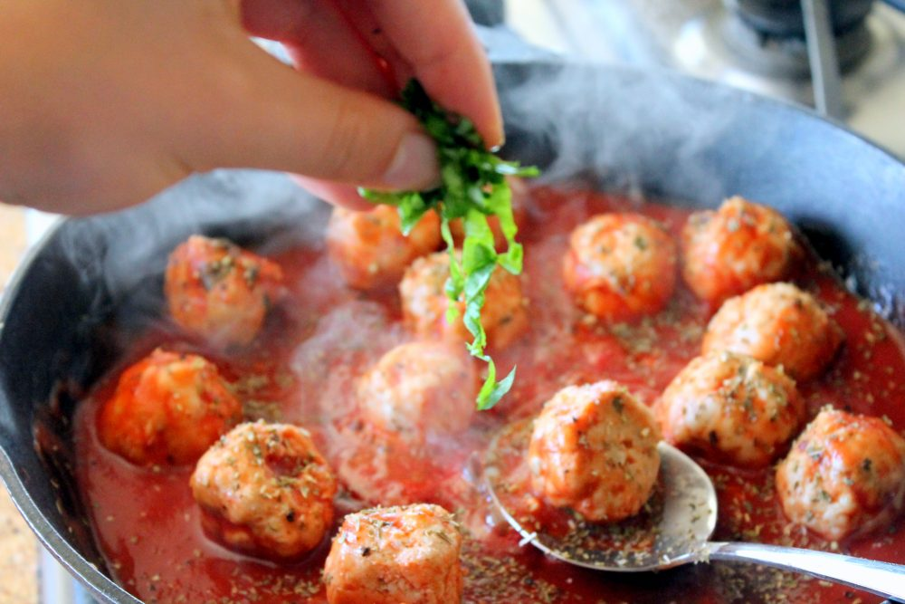 Sprinkling herbs into a skillet of turkey meatballs in spicy tomato basil sauce