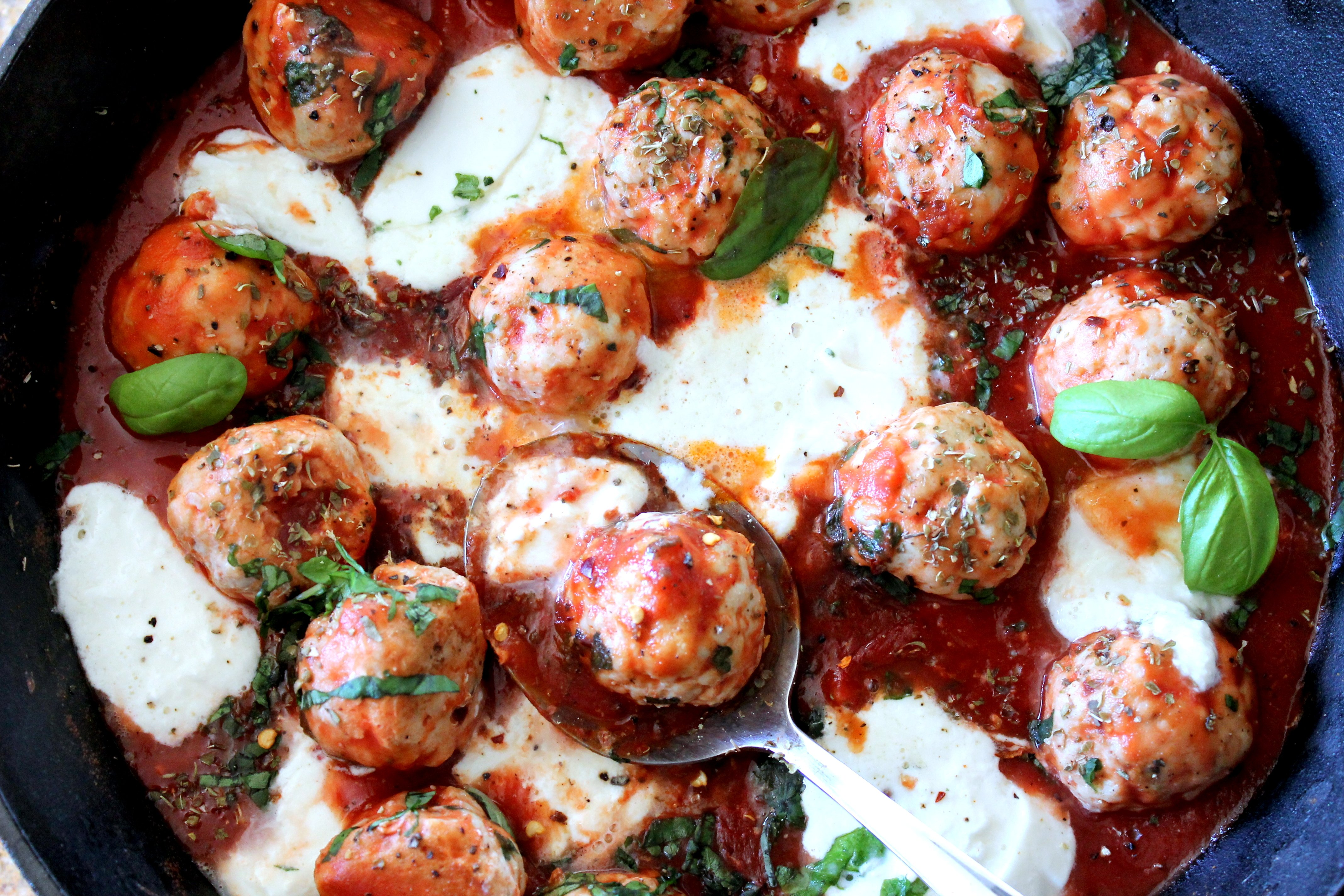 Pan of meatballs with red sauce and white cheese