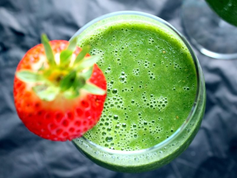 Green monster smoothie in a glass with a strawberry