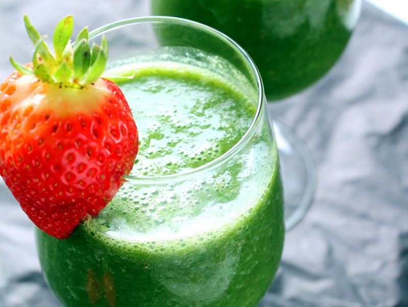 Green monster smoothie in a glass with a strawberry on the side