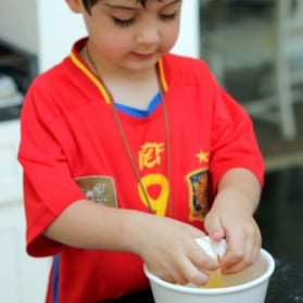 Young boy cracking an egg into a bowl